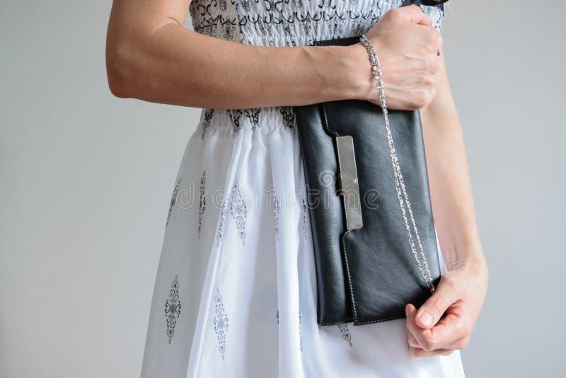 Den främre skördsikten av den unga trendiga kvinnan klädde med den långa klänningen och rymmer en handväska arkivbild