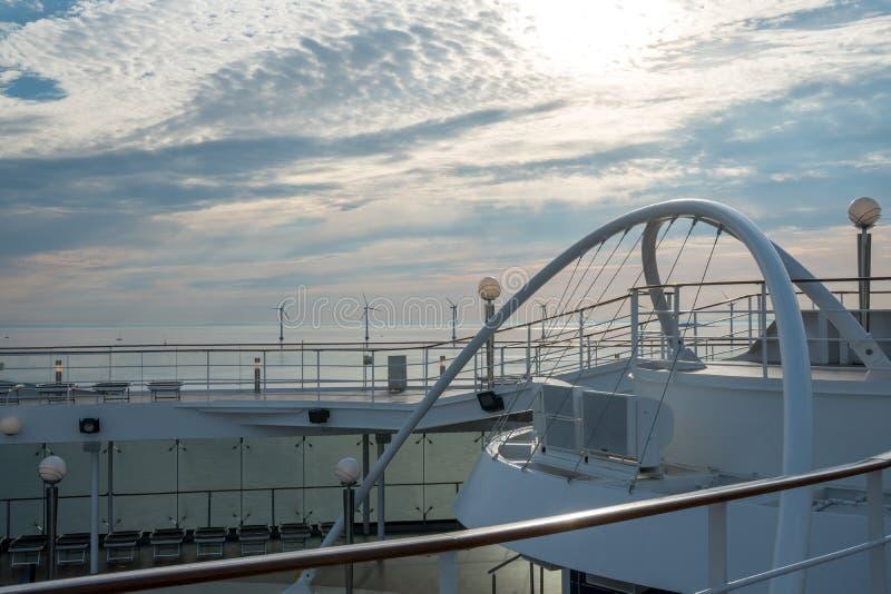 Den frånlands- väderkvarnen parkerar alternativ energi väderkvarnar i havet bak kryssningskeppet royaltyfri foto