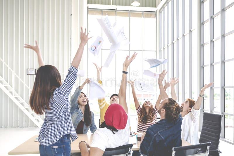 Den franka gruppen av ung idérik laganställdprople som kastar dokument, skyler över brister och känner sig lycklig efter arbetsfr royaltyfria foton