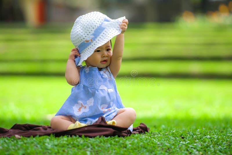 den franka ståenden av söt och förtjusande asiatisk korean behandla som ett barn flicka 3, eller 4 månader gammalt spela med hatt royaltyfri foto