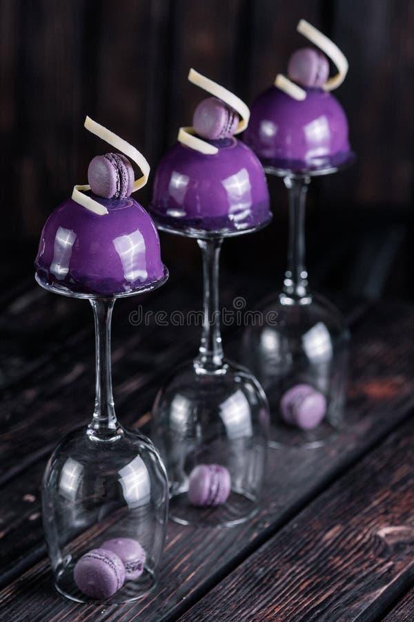Den franska blåbärmoussekakan tjänade som på inverterade vinexponeringsglas på wood bakgrund arkivfoton