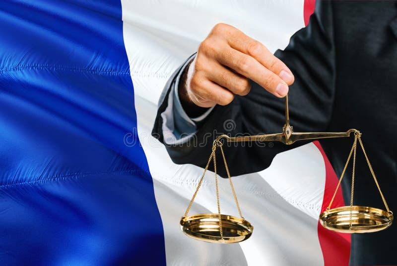 Den franska domaren rymmer guld- våg av rättvisa med Frankrike vinkande flaggabakgrund Jämställdhettema och lagligt begrepp royaltyfri bild