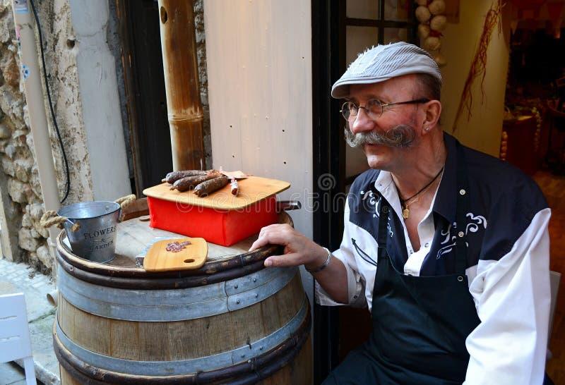 Den franska säljaren inviterar turister att smaka korvar arkivbild