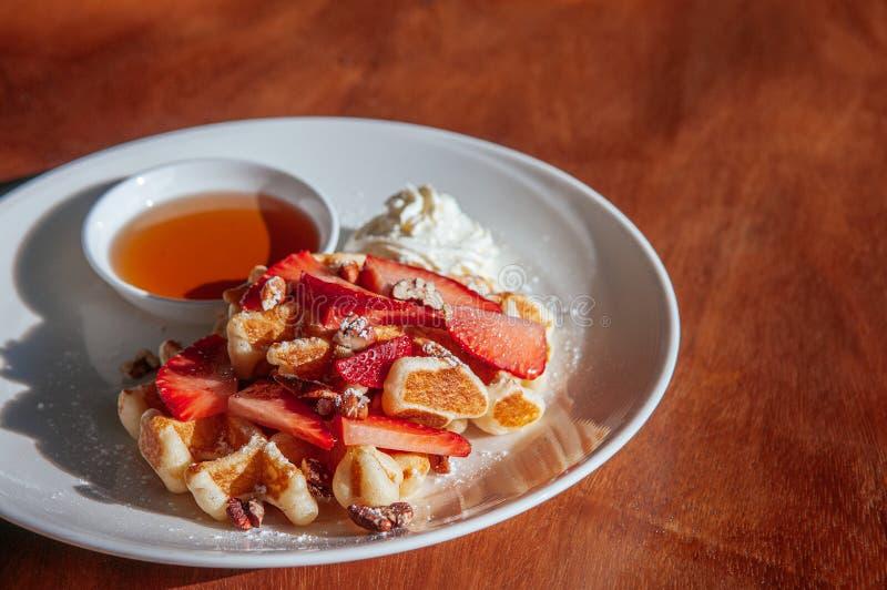 Den frasiga dillanden med nya jordgubbar bakade valnötter vispgrädde och honung arkivfoton