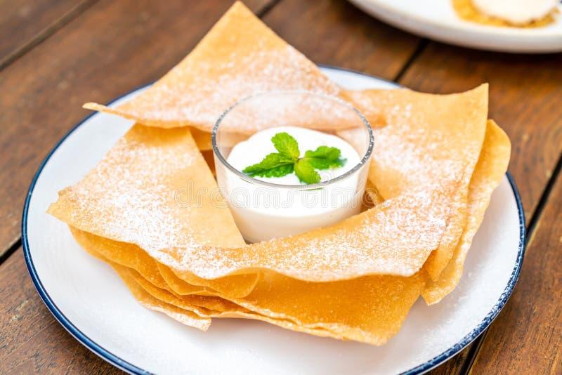 den frasiga rotien med mjölkar och vit chokladsås royaltyfri foto
