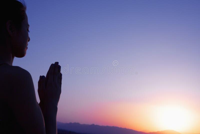 Den fridfulla unga kvinnan med händer i bön poserar tillsammans i öknen i Kina, konturn, solinställning royaltyfri bild
