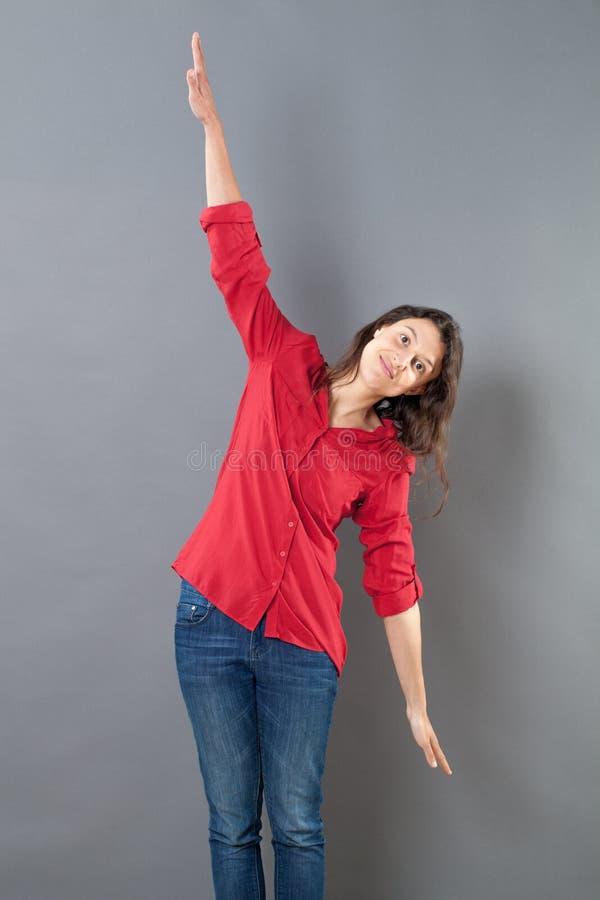 Den fridfulla unga kvinnan som använder hennes armar, öppnar vitt för att flyga fotografering för bildbyråer