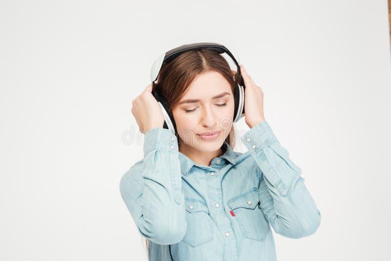 Den fridsamma fundersamma nätta kvinnan med ögon stängde att lyssna till musik arkivfoton