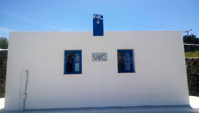 Den fristående byggnadstoaletten i vit-blått färgar på ön av Santorini royaltyfri bild
