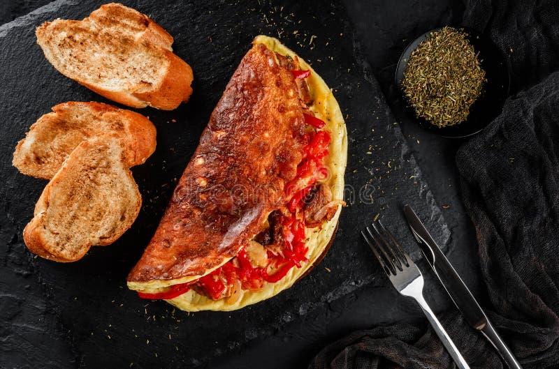 Den frodiga omelettet med kött, grönsaker, ost och örter på svart kritiserar över mörk bakgrund Bästa sikt för sund frukost, lekm royaltyfri foto