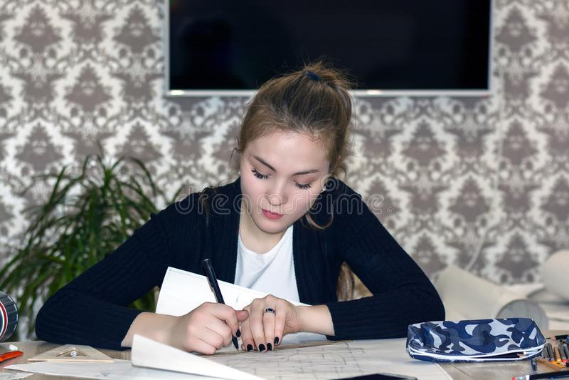 Den Frontal ståenden av en ung kvinnlig student är förlovad på tabellattraktionerna skissar, skissar, plan, arkitektur utbildning royaltyfria foton