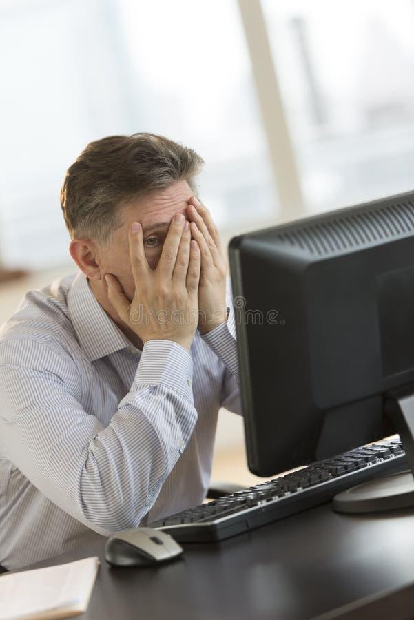 Den frustrerade affärsmannen With Hands On vänder mot att se datoren fotografering för bildbyråer