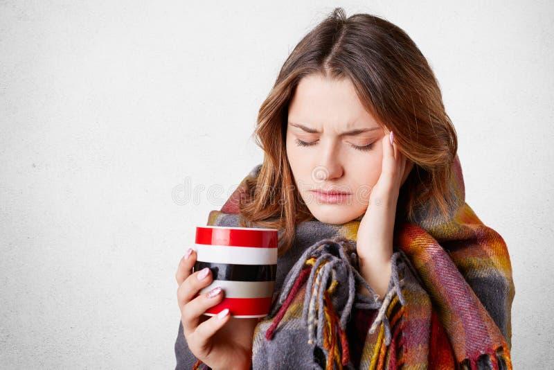 Den frustrerade dåligt unga kvinnan som täckas i den varma filten, uppehällehand på templet, lider från ruskig huvudvärk, dricker royaltyfria foton