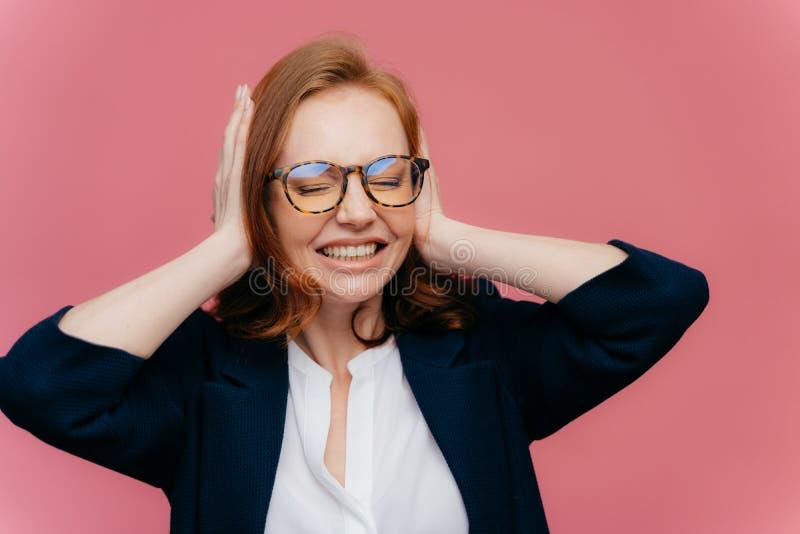 Den frustrerade unga affärskvinnan har huvudvärk, ignorerar högt oväsen, täcker öron med händer, tagtänder, har stängt ögon, bär arkivfoto