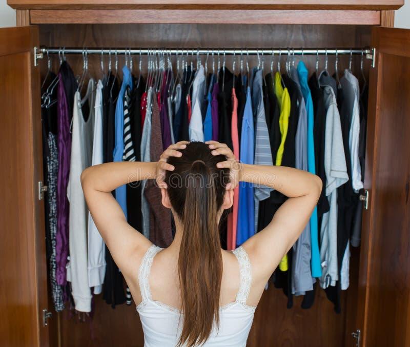 Den frustrerade unga kvinnan kan inte avgöra vad för att bära från hennes garderob arkivfoton