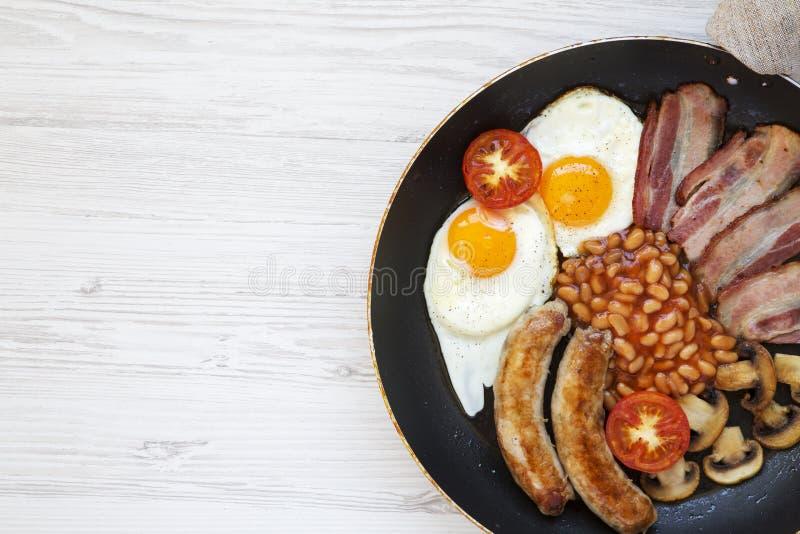 Den fulla engelska frukosten i matlagningpanna med korvar, champinjoner, stekte ägg, bönor, tomaten och bacon på en vit träbakgru royaltyfri fotografi