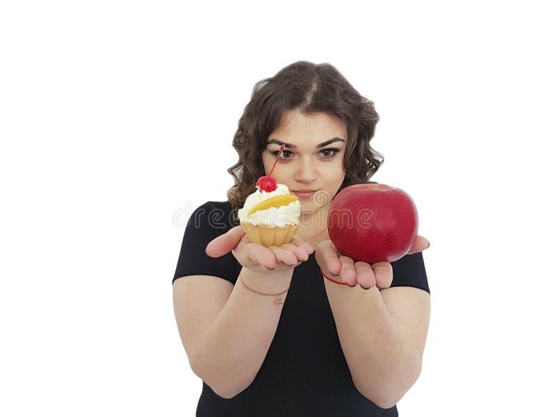 Den fulla flickan som väljer kakan, och äpplet isolerat dilemma motstår royaltyfria bilder