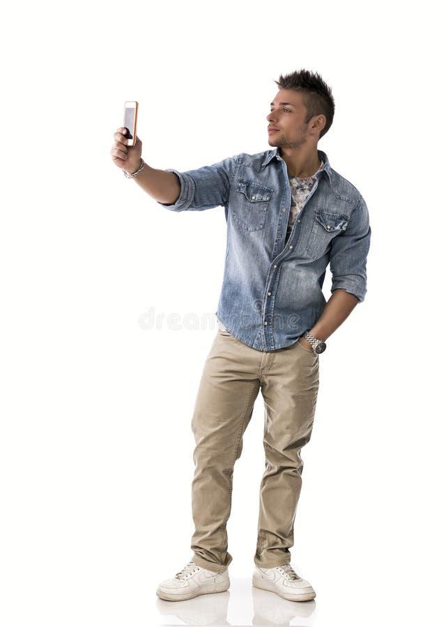Den fulla kroppen sköt av den unga mannen som tar fotoet med mobiltelefonen royaltyfri fotografi