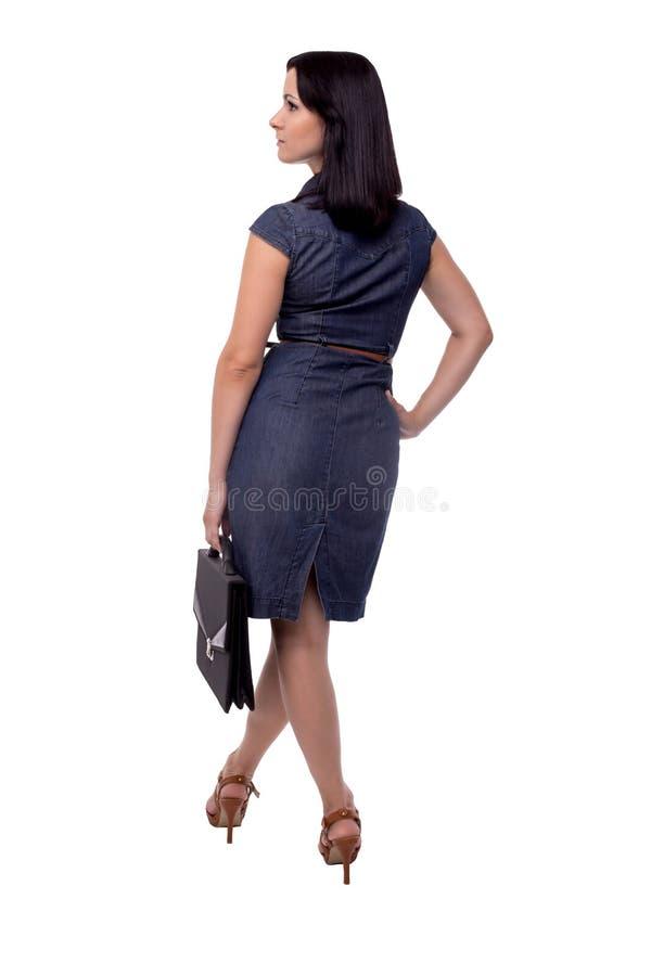 Den fulla kroppståenden av affärskvinnan i klänning tillbaka beskådar med portföljen, portföljen som isoleras på vit royaltyfri bild