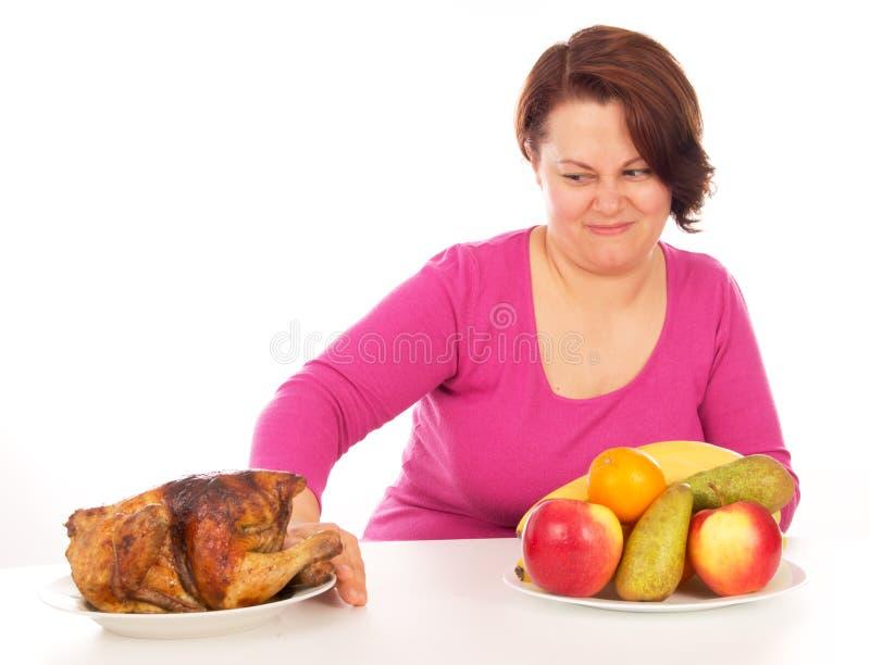 Den fulla kvinnan önskar inte att äta höna arkivfoton
