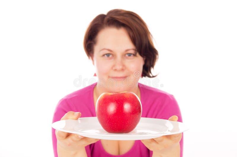 Den fulla kvinnan erbjuder äpplet arkivfoto