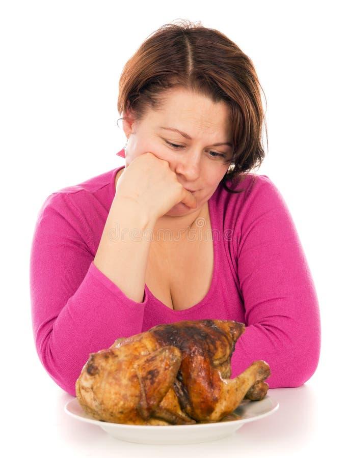 Den fulla kvinnan på en banta, önskar att äta höna fotografering för bildbyråer
