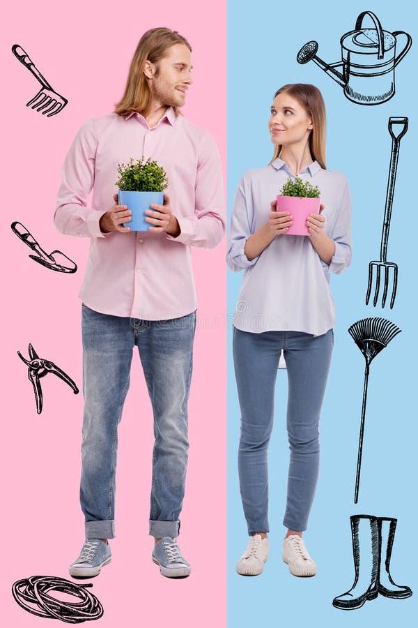Den fulla längden av älskvärda par med krukan blommar royaltyfri foto