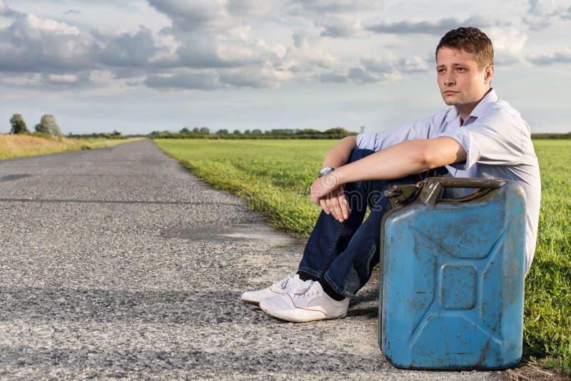 Den fulla längden av den unga mannen med tom gas kan sammanträde vid vägen arkivfoton