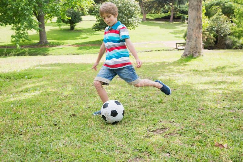 Den fulla längden av en pojke som sparkar bollen på, parkerar royaltyfria foton