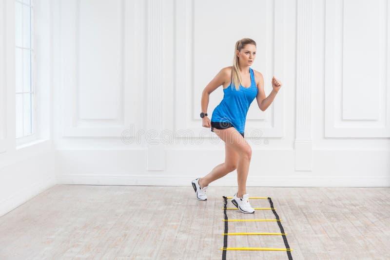 Den fulla längden av den sportiga härliga unga idrotts- blonda kvinnan i svarta kortslutningar och den blåa överkanten är den car fotografering för bildbyråer