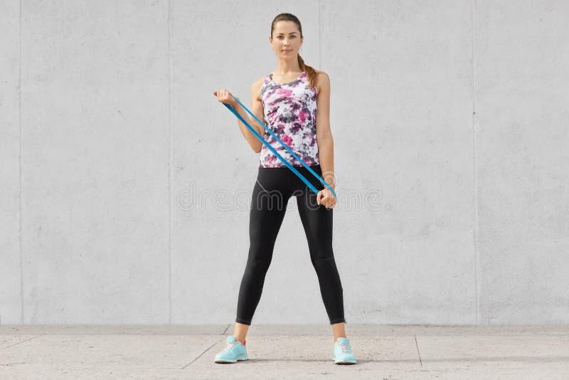 Den fulla längden som skjutas av attraktiv slank kvinna i sportswear, gör armövningar med konditiongummi, den elastiska musikband royaltyfri foto