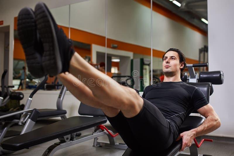 Den fulla längdståenden av den muskulösa byggandemannen, medan göra ben, trycker på övning i konditionmitt royaltyfri foto