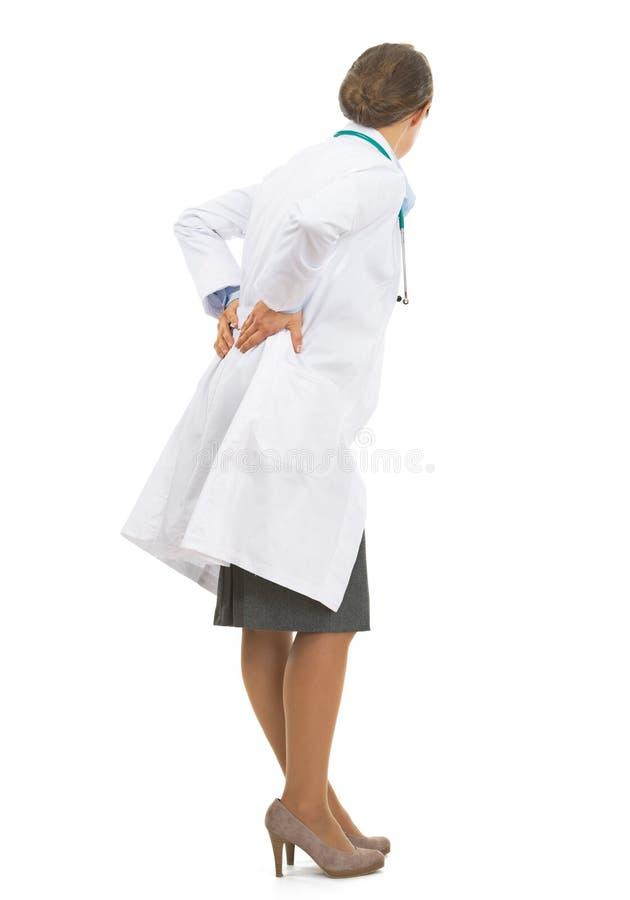 Den fulla längdståenden av doktorskvinnan med tillbaka smärtar royaltyfri fotografi