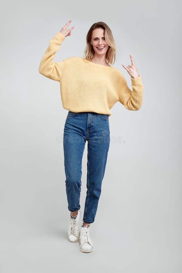 Den fulla längdståenden av en ung blond kvinnavisning vaggar gest med händer som isoleras över grå bakgrund Ikl?tt tillf?lligt royaltyfria foton