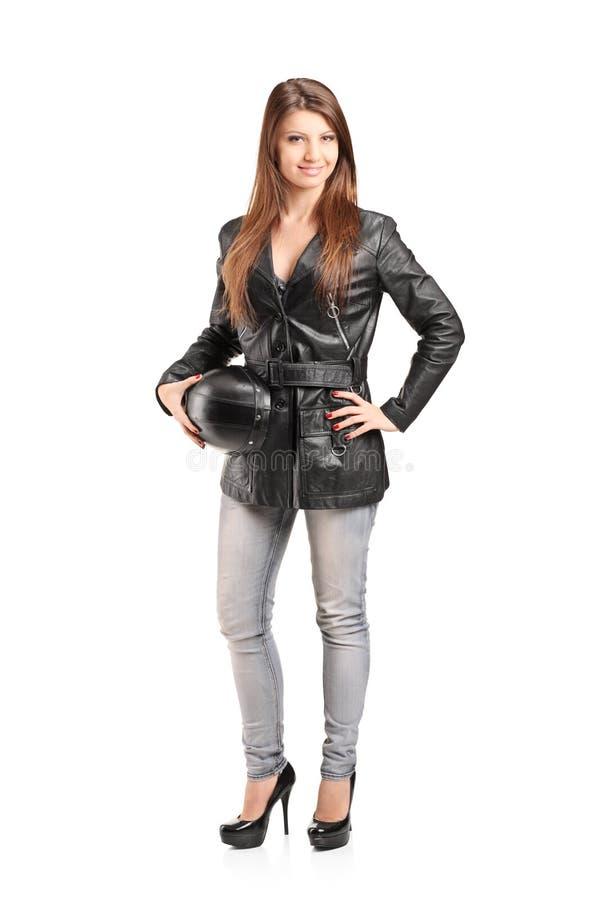 Den fulla längdståenden av en ung kvinnlig cyklist i ett läder klår upp arkivfoton