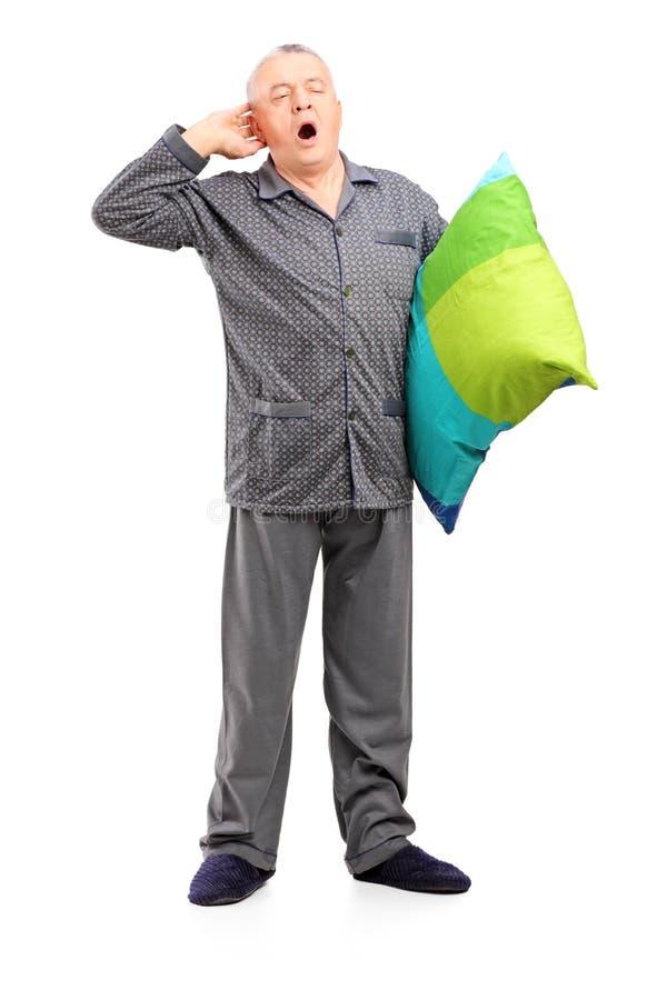 Den fulla längdståenden av ett sömnigt mognar manen i pajamasinnehav a royaltyfria bilder