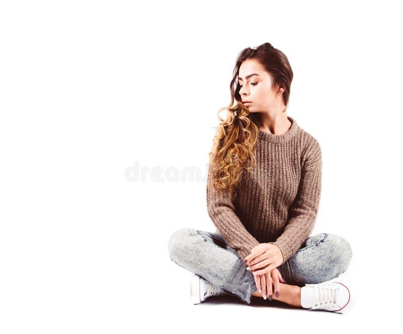 Den fulla längdståenden av flickan som bär det bruna omslaget och jeans som placeras poserar på vit bakgrund royaltyfria foton