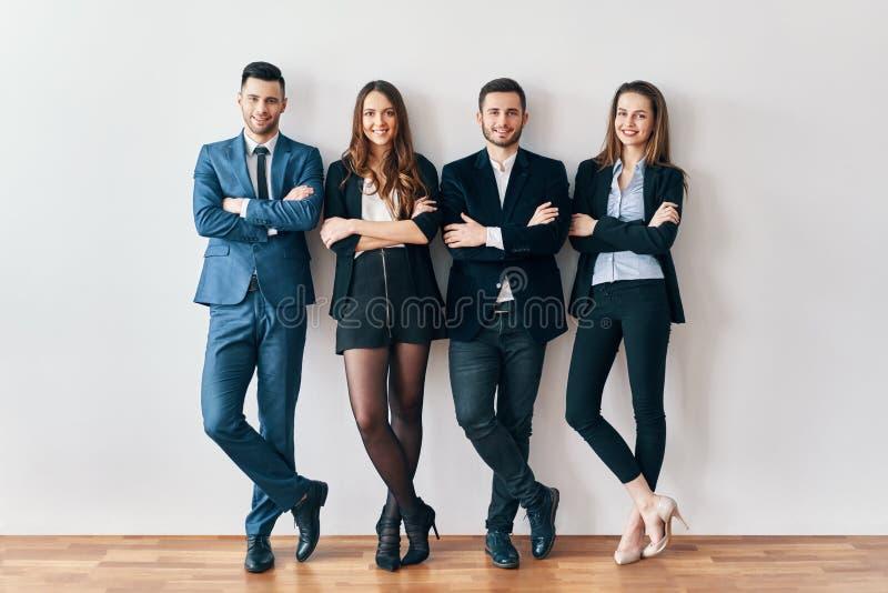 Den fulla längdståenden av ungt och le affärsfolk med armar korsade lutar till väggen i regeringsställning royaltyfria foton