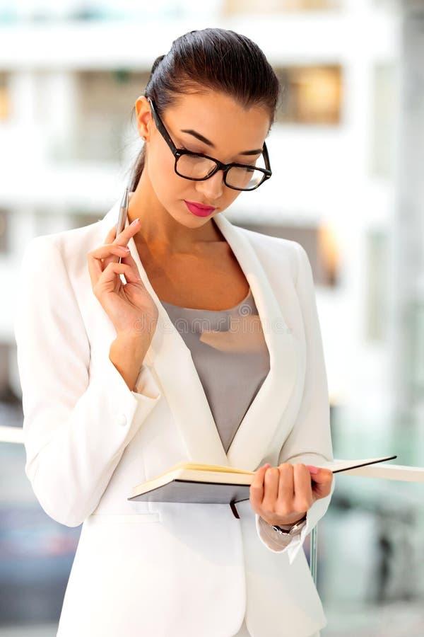 Den fundersamma affärskvinnan ser i hennes anteckningsbok royaltyfri fotografi