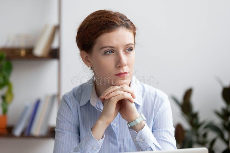 Den fundersamma allvarliga eftertänksamma affärskvinnan förlorade djupt i tankar på arbete arkivbild