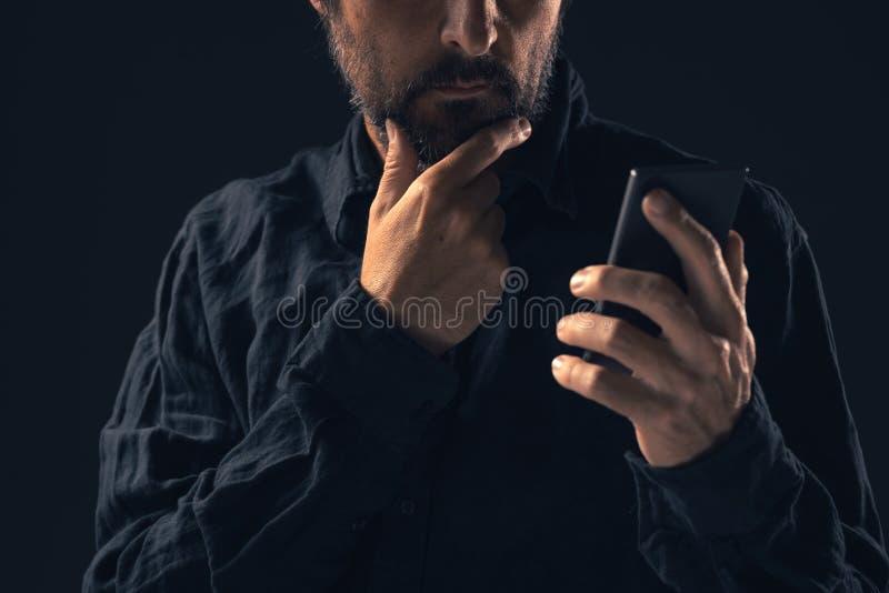 Den fundersamma bekymrade mannen läser textmeddelandet på smartphonen royaltyfri fotografi