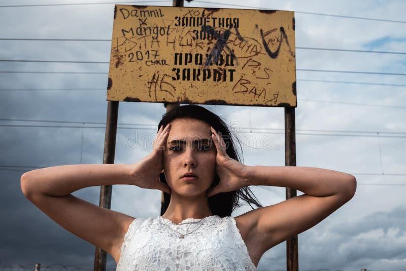 Den fundersamma belastade unga kvinnan rymmer hon hennes huvud i hennes händer arkivfoton