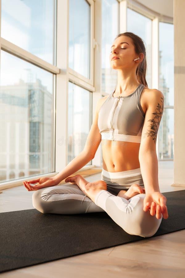 Den fundersamma damen i sportig överkant och damasker i lotusblomma poserar att meditera på yoga som är matt över stort fönster arkivfoton