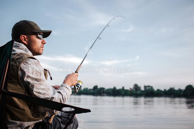 Den fundersamma grabben sitter på kanten av vatten och ser till rätten Han rymmer den klipska stången i händer Det är aftonen och royaltyfri fotografi