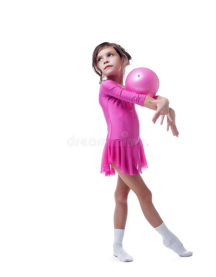 Den fundersamma lilla gymnasten utför med bollen royaltyfri bild