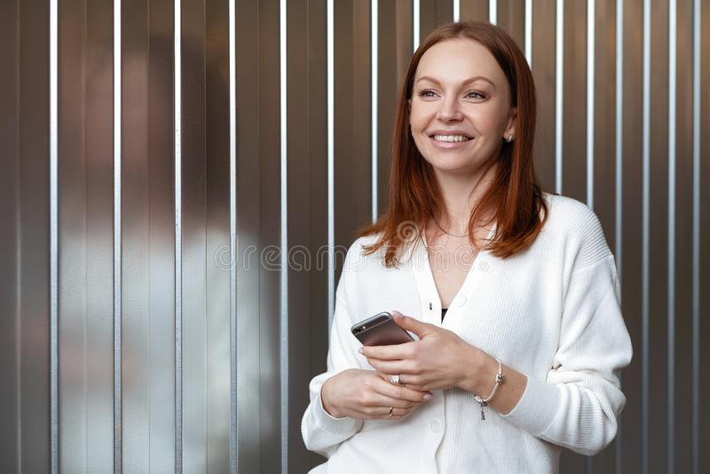 Den fundersamma nöjda kvinnan med drömlik blick, rymmer mobiltelefonen, överför textmeddelandet, bär det vita formella förklädet, fotografering för bildbyråer