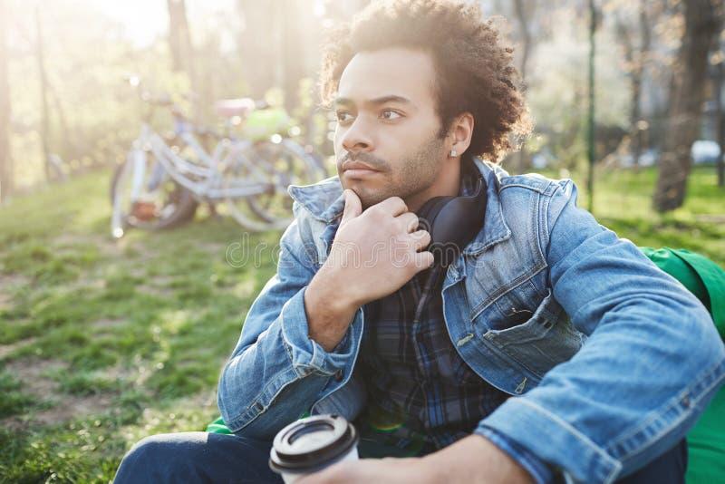 Den fundersamma stiliga mörkhyade grabben med den rörande hakan för borstet, medan sitta på stol för bönapåse, parkerar in och at royaltyfria bilder