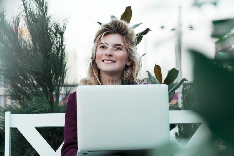 Den fundersamma unga kvinnan i exponeringsglas genom att anv?nda en dator som sitter p? en b?nk i en stad, parkerar Begreppet av  royaltyfri bild