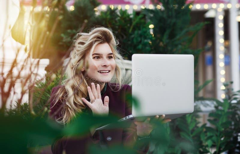 Den fundersamma unga kvinnan i exponeringsglas genom att anv?nda en dator som sitter p? en b?nk i en stad, parkerar Begreppet av  royaltyfria bilder