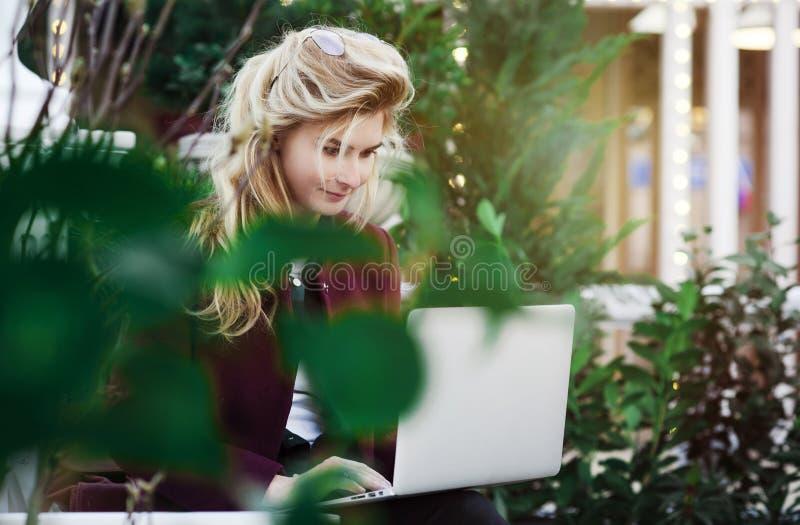 Den fundersamma unga kvinnan i exponeringsglas genom att anv?nda en dator som sitter p? en b?nk i en stad, parkerar Begreppet av  royaltyfria foton